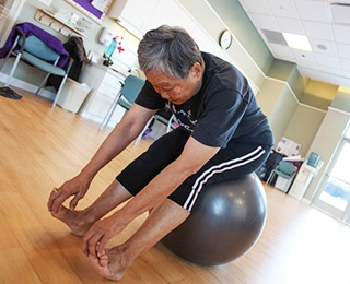 older adult woman instructor from the Admiral stretching on exercise ball