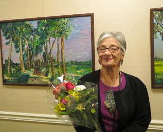 older adult woman smiling and holding flowers