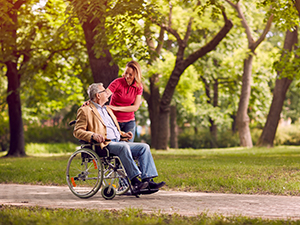 Caregiver walking her older father in the park