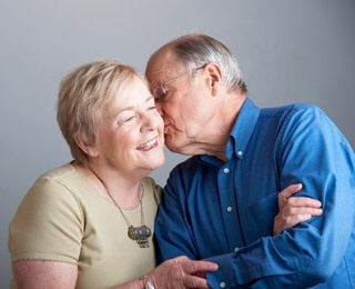 an older gentleman giving his wife a kiss on the cheek