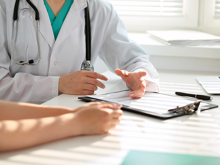 Doctor sitting at desk with patient discussing healthcare options