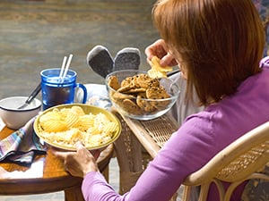 Woman at home stress eating chips and cookies